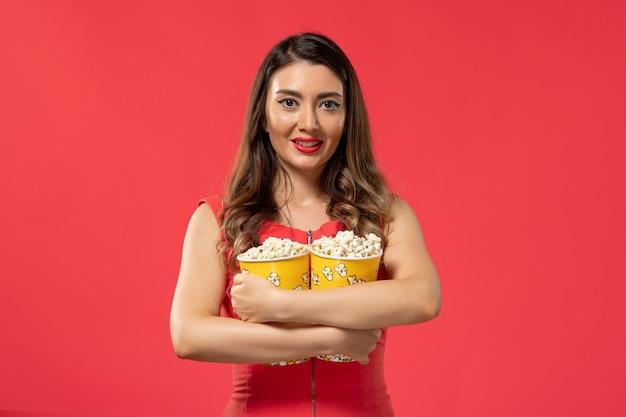 Vooraanzicht jong wijfje dat popcornpakketten houdt en op het rode oppervlak glimlacht