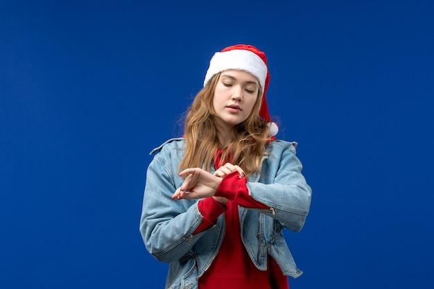 Vooraanzicht jong wijfje dat tijd op blauwe achtergrondkleur van de kerstmisemotie controleert