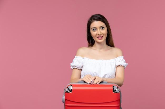 Vooraanzicht jong wijfje dat voor vakantie voorbereidingen treft die op roze achtergrond de vrouw van de de reisreis van de achtergrondreis in het buitenland glimlachen