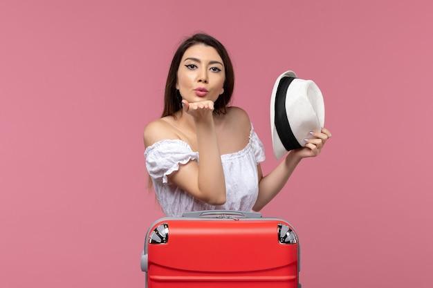 Vooraanzicht jong wijfje dat voor vakantie voorbereidingen treft en luchtkussen op roze reis als achtergrond verzendt in het buitenland reizende zeereis