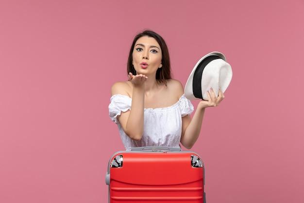 Vooraanzicht jong wijfje dat voor vakantie voorbereidingen treft het verzenden van luchtkussen op roze achtergrondreis reizende zeereis in het buitenland reis
