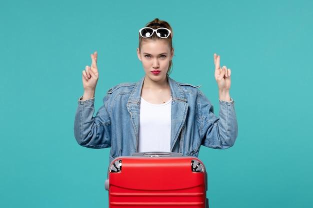 Vooraanzicht jong wijfje dat zich voor reis klaarmaakt die haar vingers kruist op blauwe ruimte