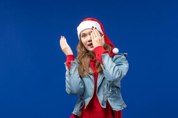 Vooraanzicht jong wijfje die de helft van haar gezicht op blauwe achtergrondkleur van kerstmisemoties behandelen