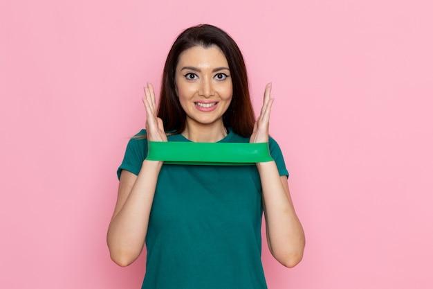 Vooraanzicht jong wijfje die groen verband houden en op lichtroze muuroefening sport training atleet schoonheid glimlachen