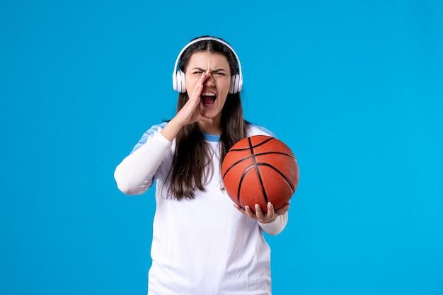 Vooraanzicht jong wijfje die met hoofdtelefoons basketbal op blauwe muur houden