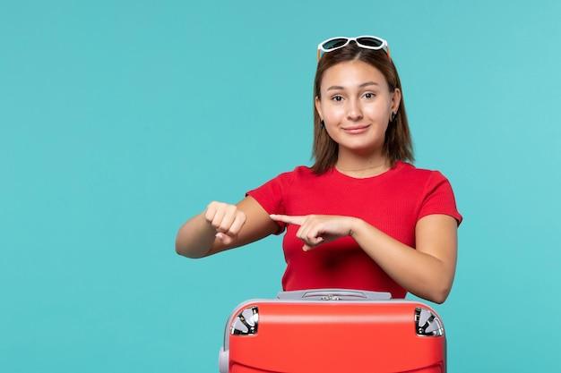 Vooraanzicht jong wijfje die met rode zak voor vakantie voorbereidingen treffen die op blauwe ruimte glimlachen