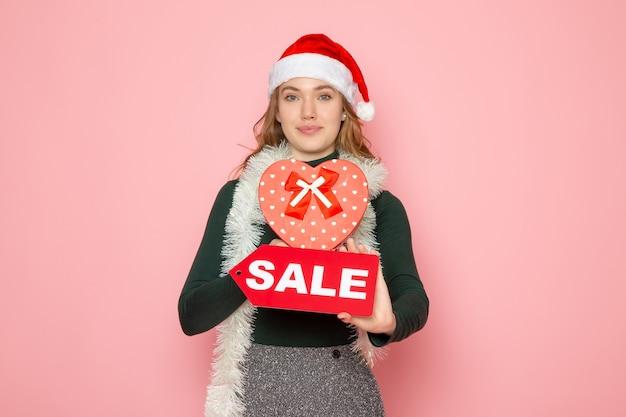 Vooraanzicht jong wijfje die rode verkoop houden die en op roze muur houden kerstmis nieuwjaar het winkelen emotievakantie