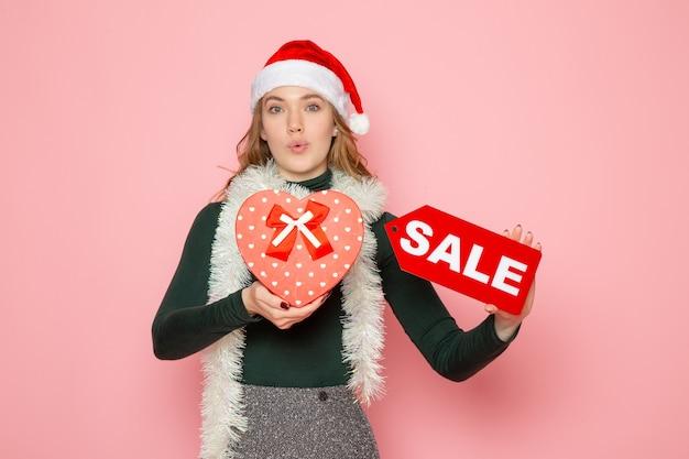 Vooraanzicht jong wijfje die rode verkoop houden die en op roze muur schrijven, kerstmis nieuwjaar winkelen mode emotie vakantie