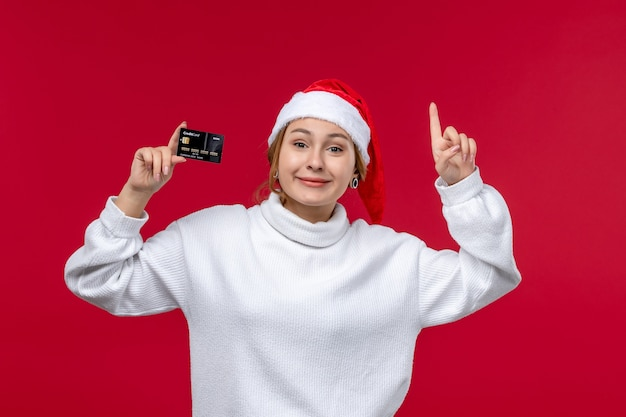 Vooraanzicht jong wijfje het glimlachen holdingsbankkaart op rode achtergrond