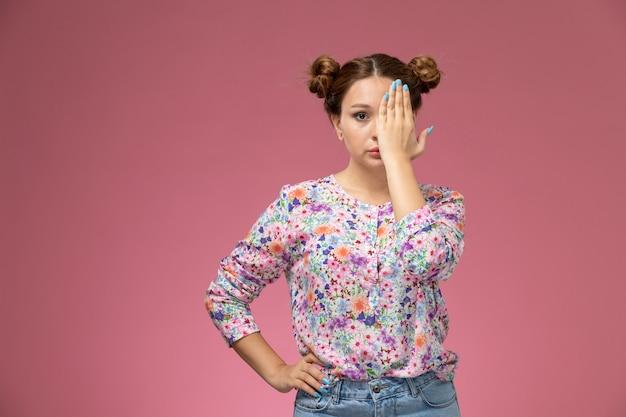 Vooraanzicht jong wijfje in bloem ontworpen overhemd en spijkerbroek die de helft van haar gezicht op de roze achtergrond bedekt