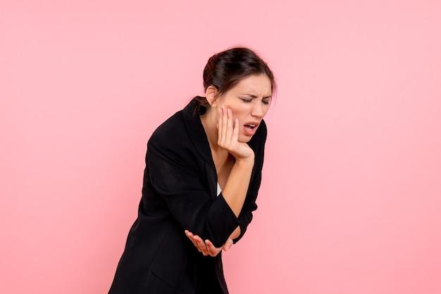 Vooraanzicht jong wijfje in donker jasje die aan kiespijn op roze achtergrond lijden