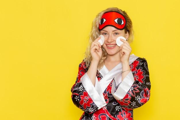 Vooraanzicht jong wijfje in nachtjas en het dragen van oogmasker die haar gezicht op gele muur schoonmaken van het de nachtbedmodel van het slaapmeisje