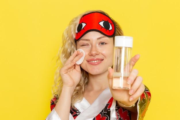 Vooraanzicht jong wijfje in nachtjas en het dragen van oogmasker die haar gezicht van samenstelling schoonmaken op geel het model van het de nachtbed van het bureauslaapmeisje