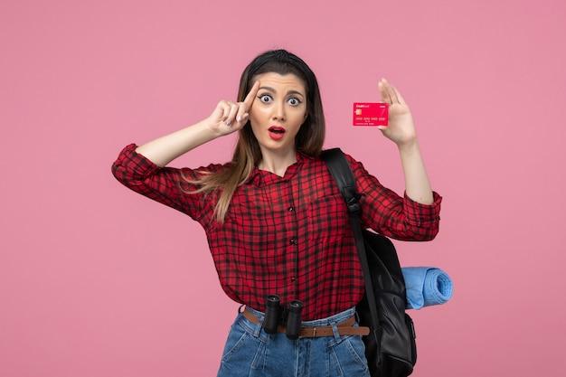 Vooraanzicht jong wijfje in rood overhemd met bankkaart op roze menselijke vrouwenkleuren als achtergrond