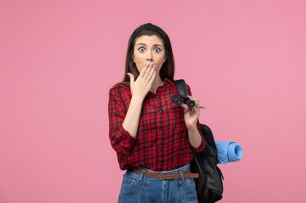 Vooraanzicht jong wijfje in rood overhemd met verrekijker op de roze vrouw van de achtergrondstudentkleur