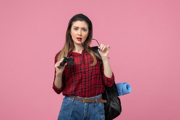 Vooraanzicht jong wijfje in rood overhemd met verrekijker op het roze model van de achtergrondvrouwenkleur
