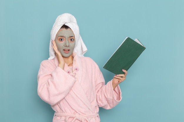 Vooraanzicht jong wijfje in roze badjas die voorbeeldenboek op de blauwe muur houden en lezen schoonheid water bad crème zelfzorg douche