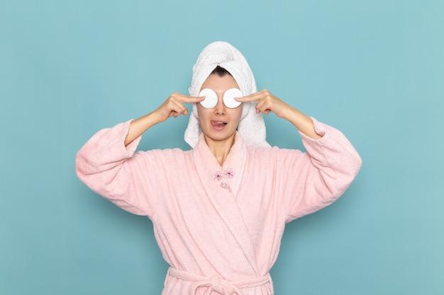 Vooraanzicht jong wijfje in roze badjas na douche die haar ogen bedekt met katoen op lichtblauwe muur schoonheidswater zelfzorgdouche schoon
