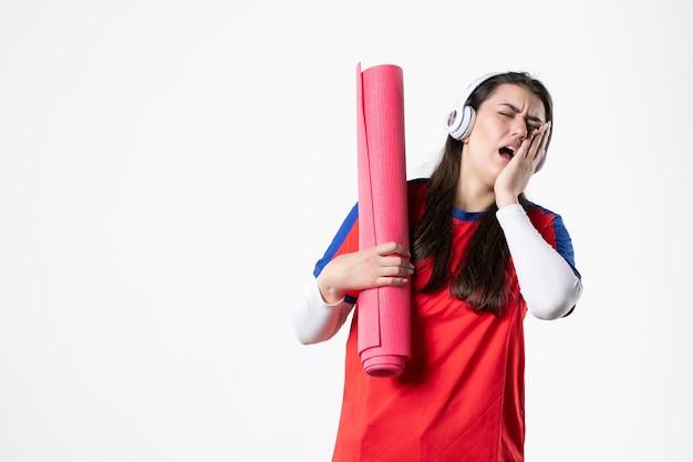 Vooraanzicht jong wijfje in sportkleren die yogamat houden en kiespijn hebben