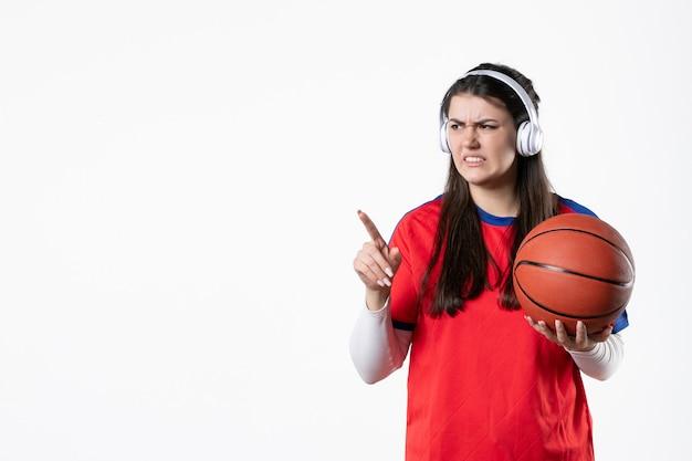 Vooraanzicht jong wijfje in sportkleren met basketbal