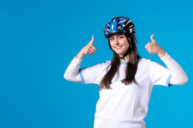 Vooraanzicht jong wijfje in sportkleren met helm op blauwe muur