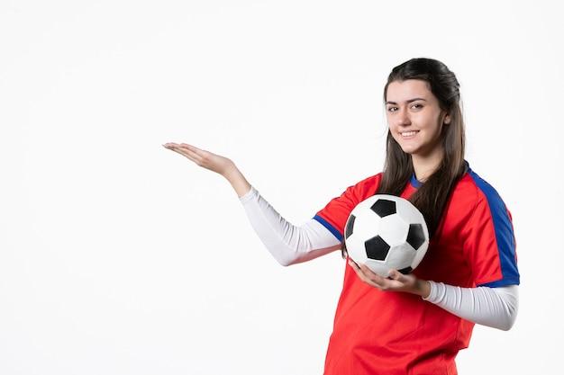 Vooraanzicht jong wijfje in sportkleren met voetbal op witte muur