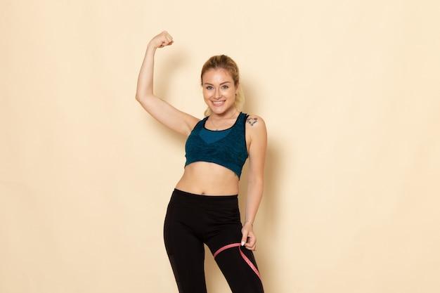 Vooraanzicht jong wijfje in sportuitrusting die haar lichaamsbuiging meten