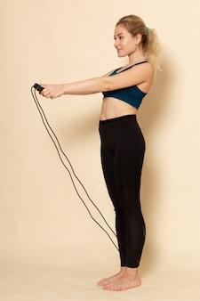 Vooraanzicht jong wijfje in sportuitrusting die oefeningen met springtouwen doen