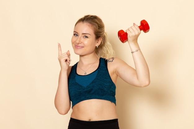 Vooraanzicht jong wijfje in sportuitrusting die rode domoren op de lichte witte training van de de gezondheidsschoonheid van het muursportlichaam houden