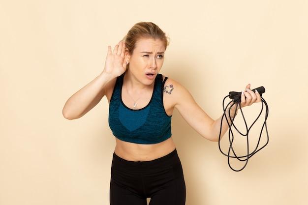 Vooraanzicht jong wijfje in sportuitrusting die touwtjespringen houden en op witte muur de oefeningen van de de lichaamssportschoonheid van de muurgezondheidstraining luisteren