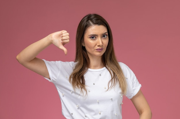 Vooraanzicht jong wijfje in wit overhemd dat in tegenstelling tot teken op de roze muur toont