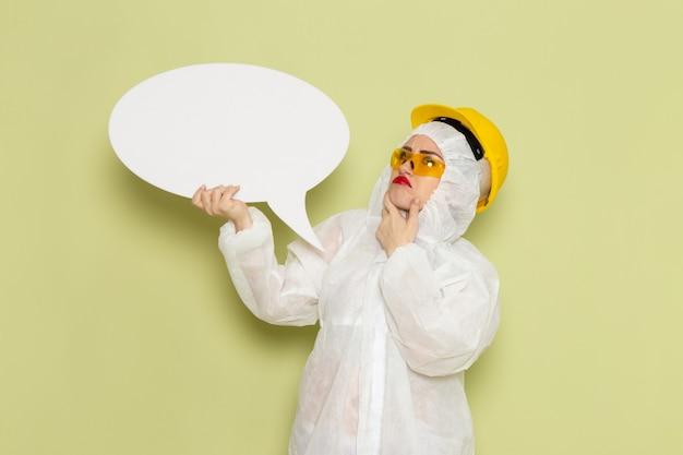 Vooraanzicht jong wijfje in wit speciaal kostuum en gele beschermende helm die groot wit teken op de groene ruimte houden