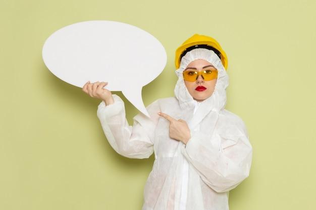 Vooraanzicht jong wijfje in wit speciaal kostuum en gele beschermende helm die groot wit teken op de groene vloer houden