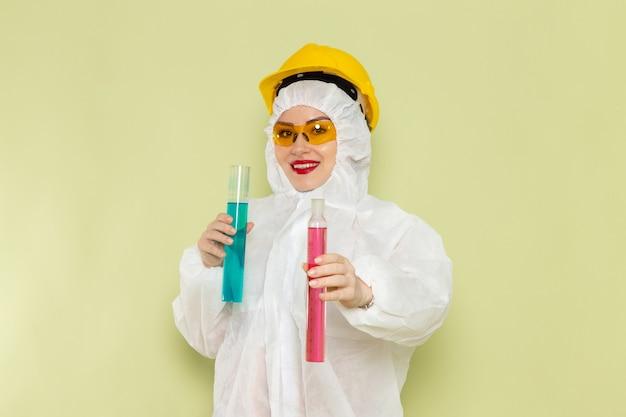 Vooraanzicht jong wijfje in wit speciaal kostuum en gele helm die chemische oplossingen op de groene ruimte houden
