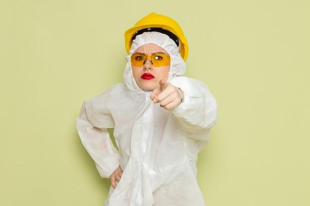 Vooraanzicht jong wijfje in wit speciaal kostuum en gele helm die op de groene ruimtebaan bedreigen