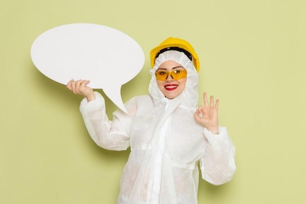 Vooraanzicht jong wijfje in wit speciaal kostuum en gele helm die wit bord met lichte glimlach op de groene ruimte houden