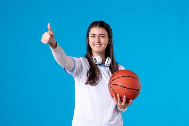Vooraanzicht jong wijfje met basketbal op blauwe muur