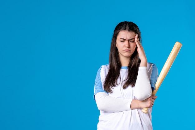 Vooraanzicht jong wijfje met honkbalknuppel op blauwe muur