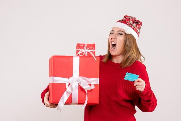 Vooraanzicht jong wijfje met kleine aanwezige kerstmis en bankkaart
