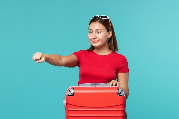Vooraanzicht jong wijfje met rode zak die zich voor vakantie klaarmaken die op blauwe ruimte glimlachen
