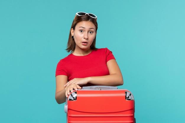 Vooraanzicht jong wijfje met rode zak die zich voor vakantie op blauw bureau klaarmaken