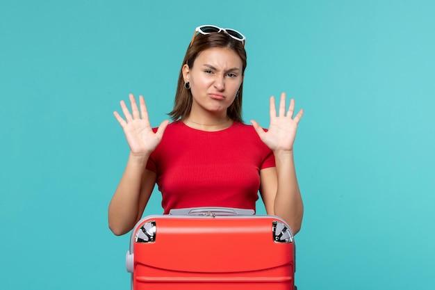 Vooraanzicht jong wijfje met rode zak die zich voor vakantie op de blauwe ruimte klaarmaken