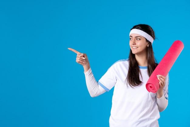 Vooraanzicht jong wijfje met yogamat op blauwe muur