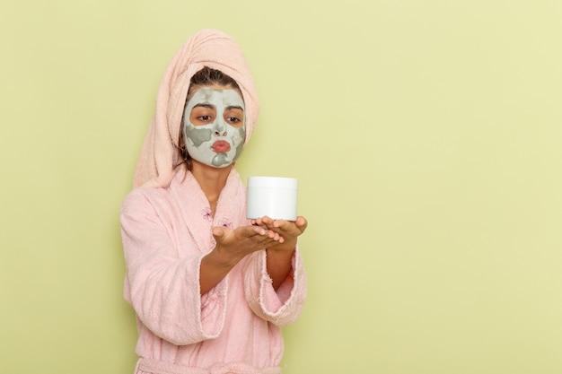 Vooraanzicht jong wijfje na douche in de roze room van de badjasholding op groene oppervlakte