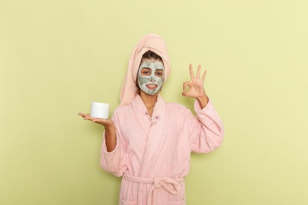 Vooraanzicht jong wijfje na douche in roze badjas die room houdt en op een groen oppervlak glimlacht
