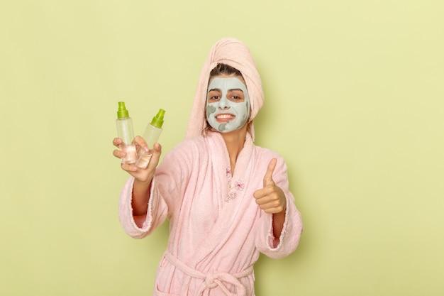 Vooraanzicht jong wijfje na douche in roze badjas met make-up verwijderaars op groen oppervlak