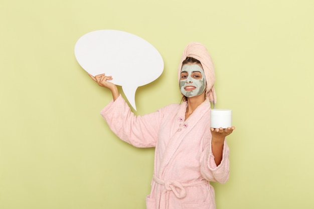 Vooraanzicht jong wijfje na douche in roze badjas met room en wit teken op groen oppervlak