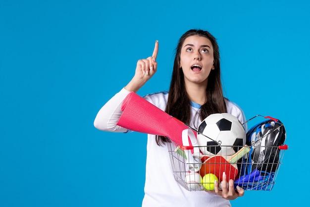 Vooraanzicht jong wijfje na sport die op blauwe muur winkelen