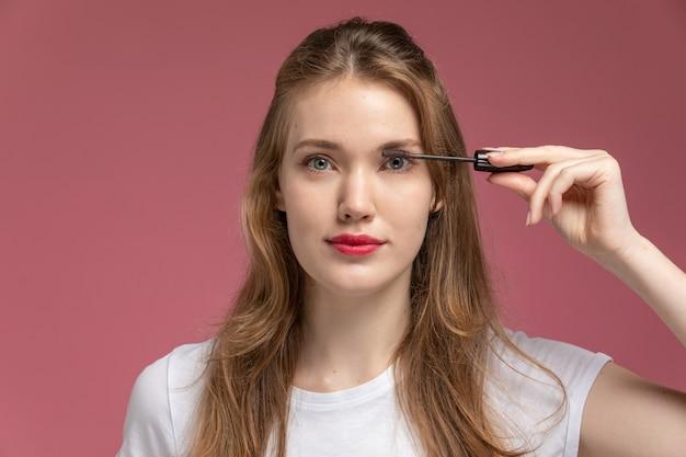 Vooraanzicht jonge aantrekkelijke vrouw doet haar make-up met mascara op donkerroze muur model kleur vrouwelijk jong meisje