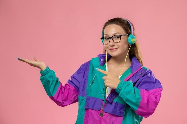 Vooraanzicht jonge aantrekkelijke vrouw in gekleurde jas luisteren naar muziek en lachend op de roze achtergrond
